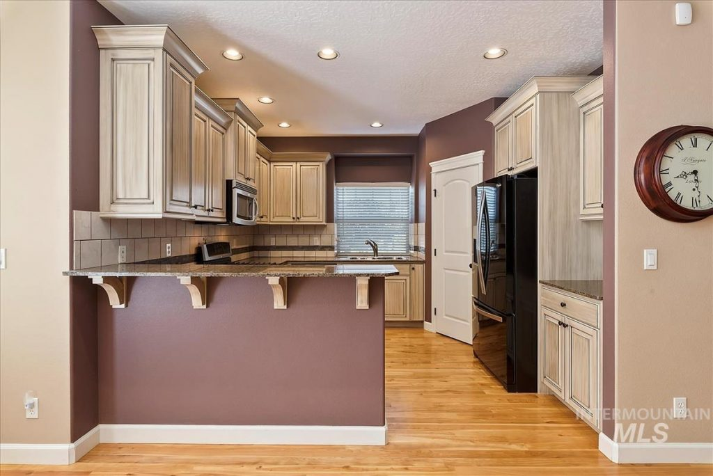 small kitchen with cream cabinets and bar counter