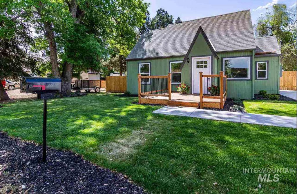 small green cottage with front deck
