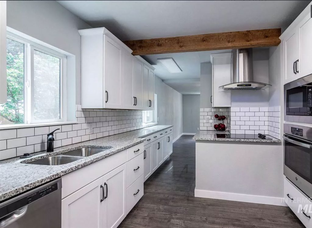 white cottage kitchen with subway tile and exposed wood beams