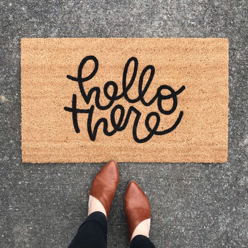 "Jute doormat with ""hello there"" in black swirly font with feet in brown booties to show scale."