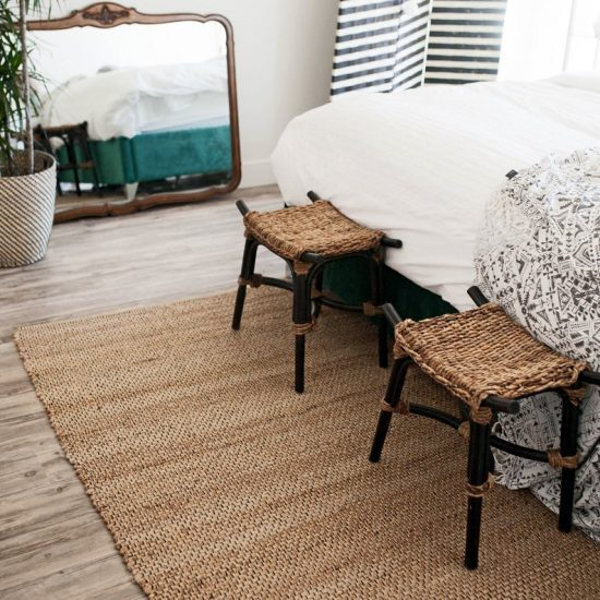 Handmade jute rug laid at the foot of the bed with two stools and across from a large mirror.