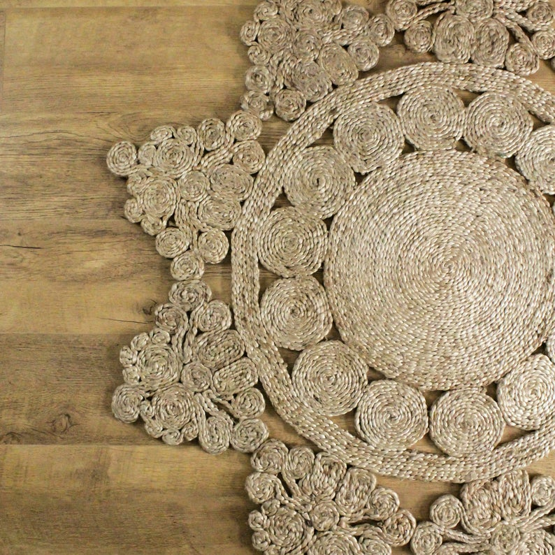 Hand woven round jute area rug laid out on a wood floor.