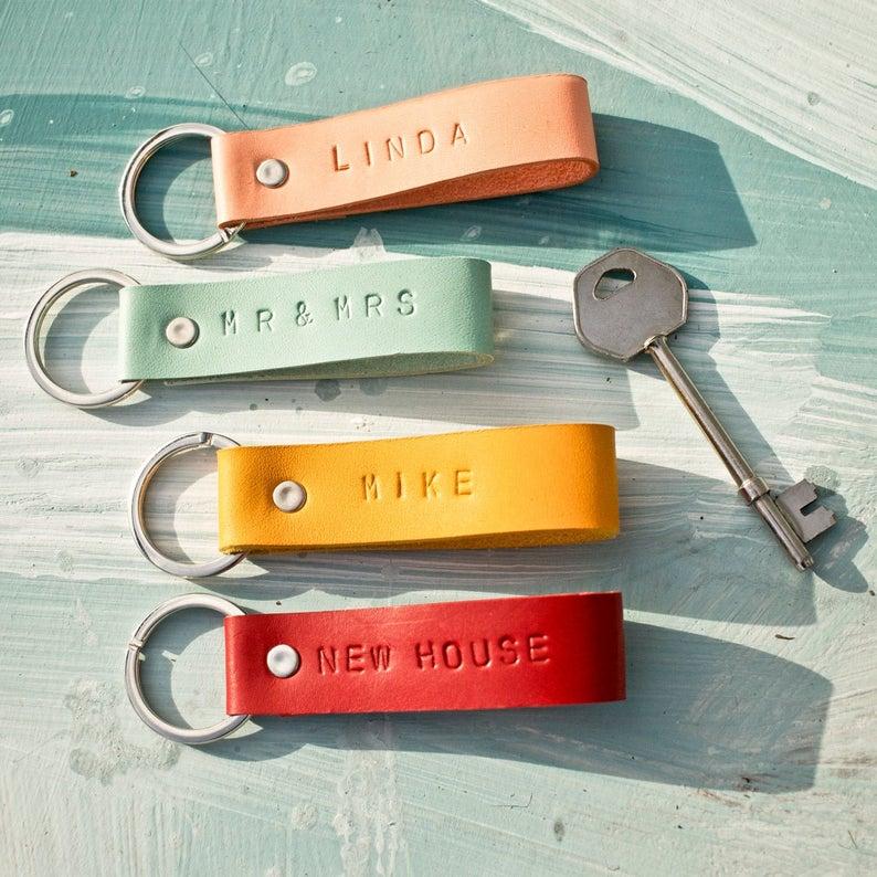 Four bright colored leather, monogrammed loops attached to a key ring arranged next to a silver key.