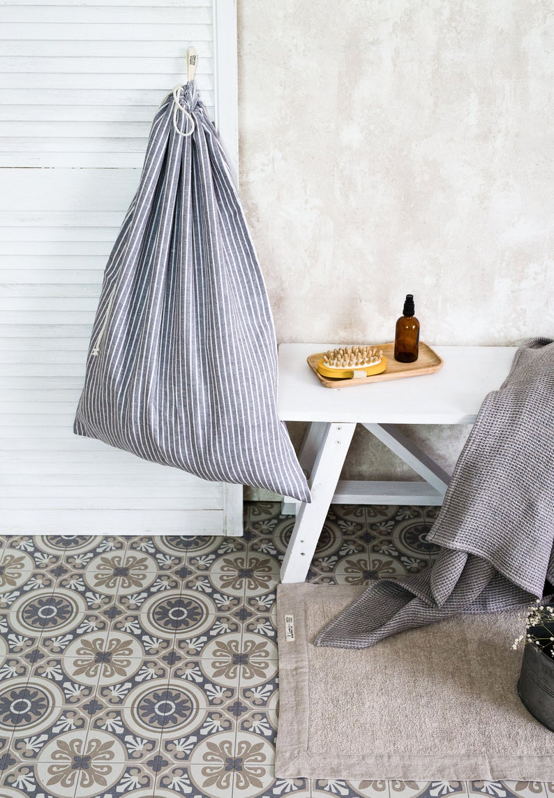 Cement tiled bathroom with a white bench and a hanging striped linen laundry bag hanging from a closet door.