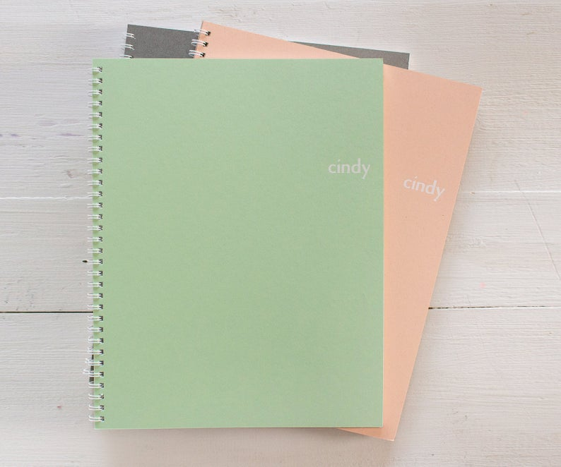 Stack of 3 spiral notebooks in gray, green and peach with monogrammed name on the cover.