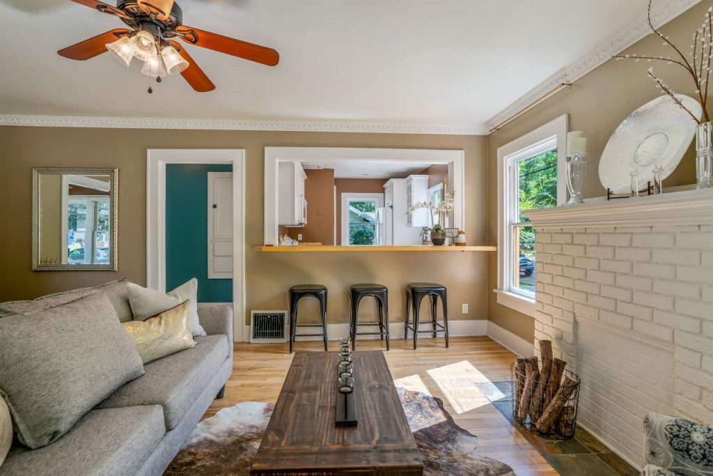 craftsman cottage living room with brick fireplace and passthrough kitchen window