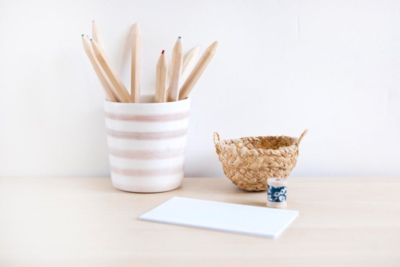 Light wood desk topped with a notepad, small basket, and a striped ceramic bowl filled with pencils.