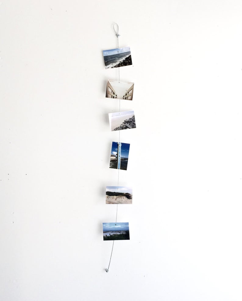 White wall with a string of hanging photos.