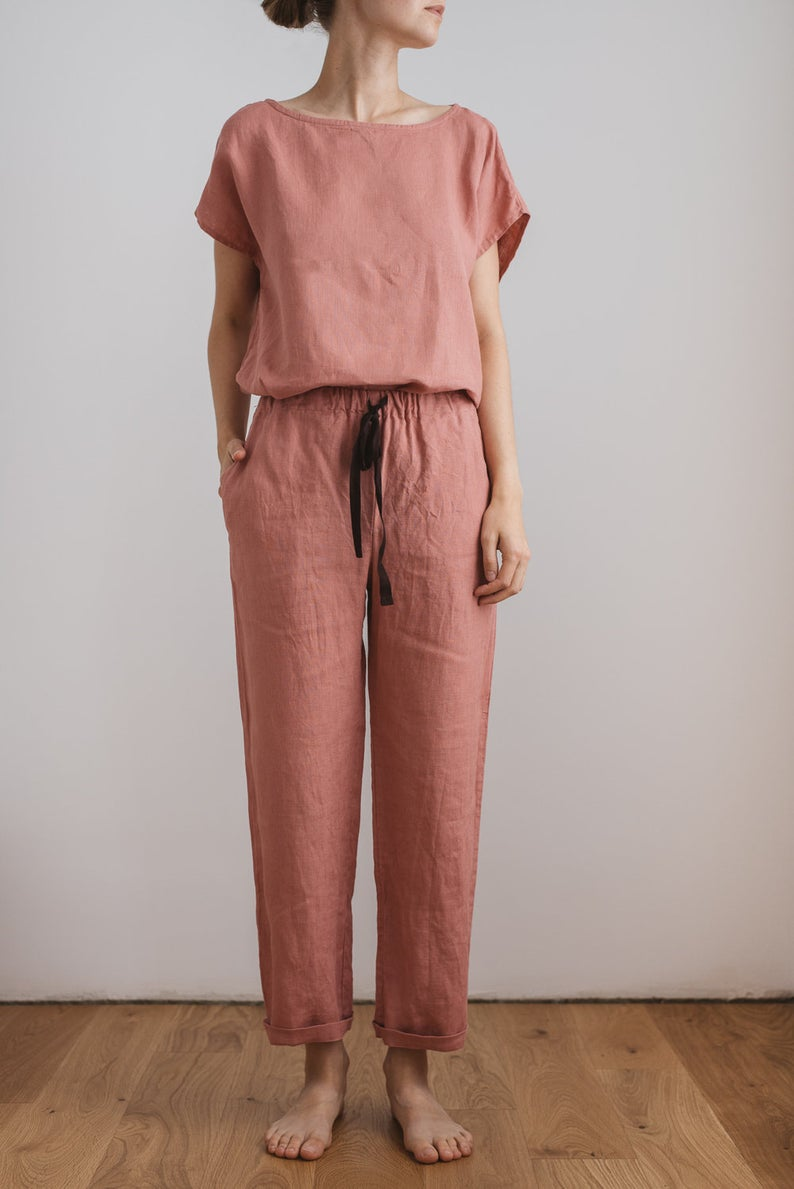 Slender woman in rose colored two piece linen pajamas with black drawstring. Dreamy jammies for your dreamy dorm.