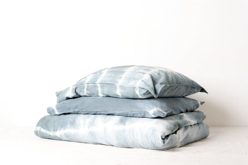 Stack of folded, light blue, tie-dye bed linens.