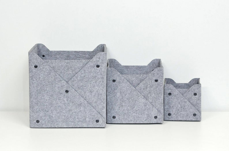 Set of three stackable, gray, wool felt storage bins with black button accents.