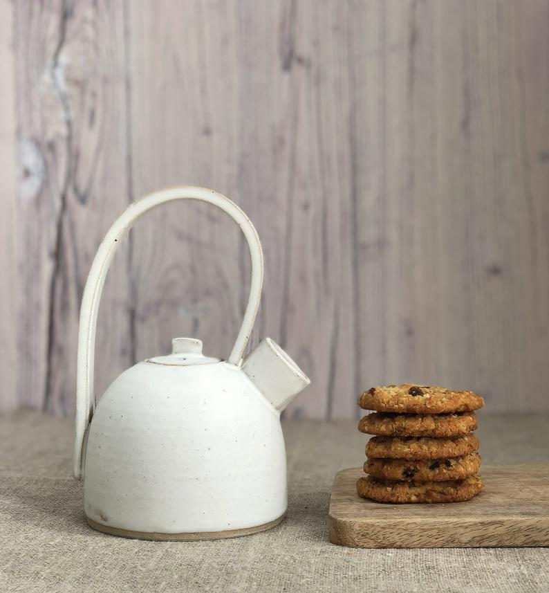White, handmade ceramic teapot with tall handle places next to a pile of homemade cookies.
