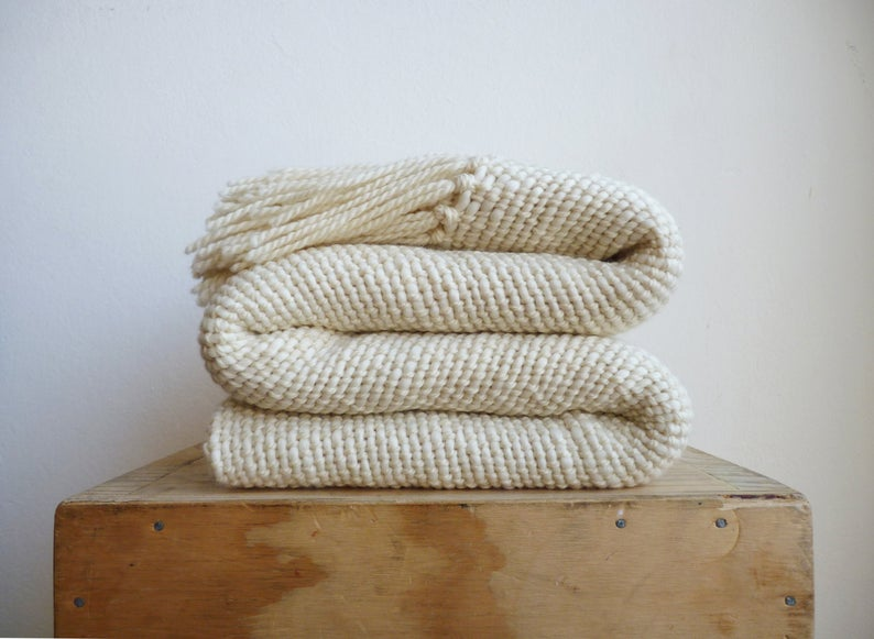 Cream colored handmade throw blanket with a fringed edge. Perfect for your dreamy dorm and folded compactly on top of a wooden box.