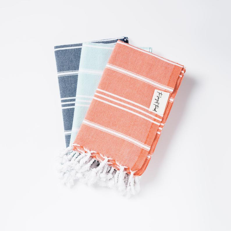 Stack of three Turkish towels in navy, light blue and coral all with white fringe.