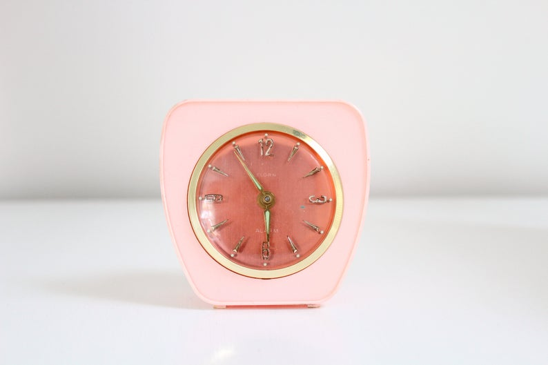 Retro pink plastic alarm clock with gold detailing.