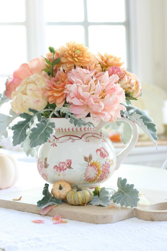 A hand-painted pitcher sitting on a wooden cutting board and filled with pink peonies and sherbet colored dahlias.
