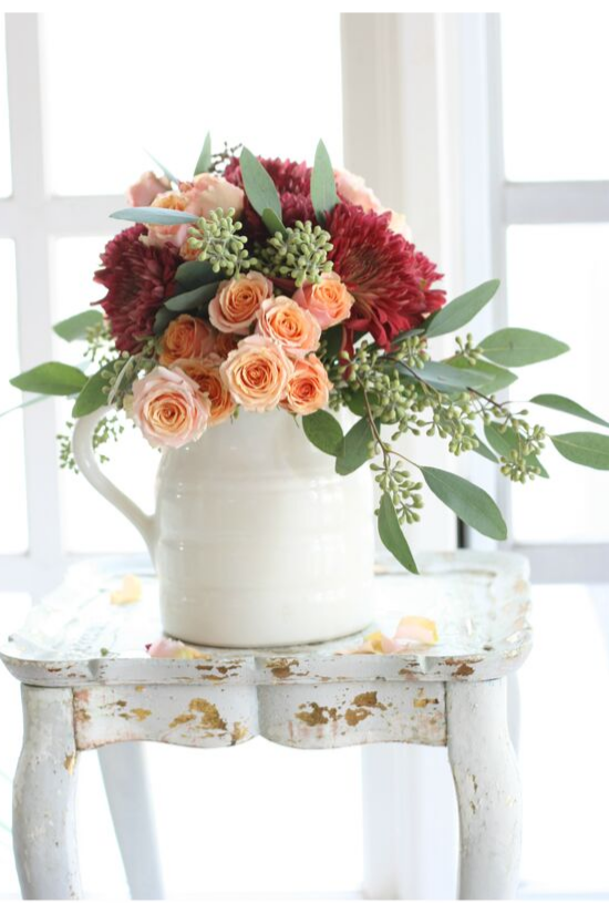White pitcher filled with dahlias, roses and eucalyptus sitting on a distressed, white, wooden side table.
