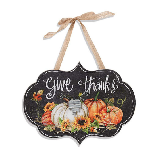 """Rustic wall hanging with a fall pumpkin and sunflower image and """"give thanks"""" in chalk cursive with a ribbon tie."""