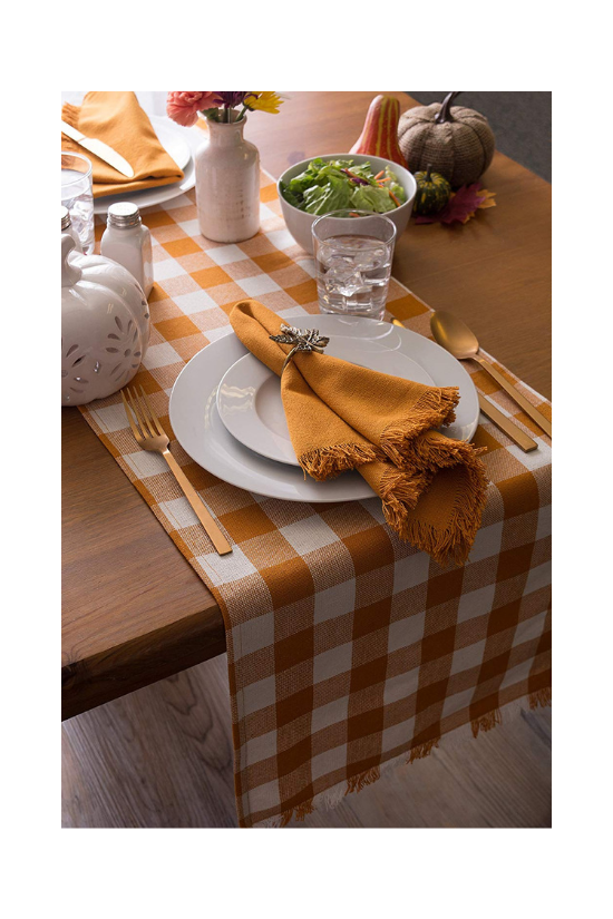 Fall table set for a dinner party featuring an orange and white checkered table runner.