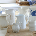 A collection of pitchers in varying shades and shapes arranged on a dining table with a linen runner.