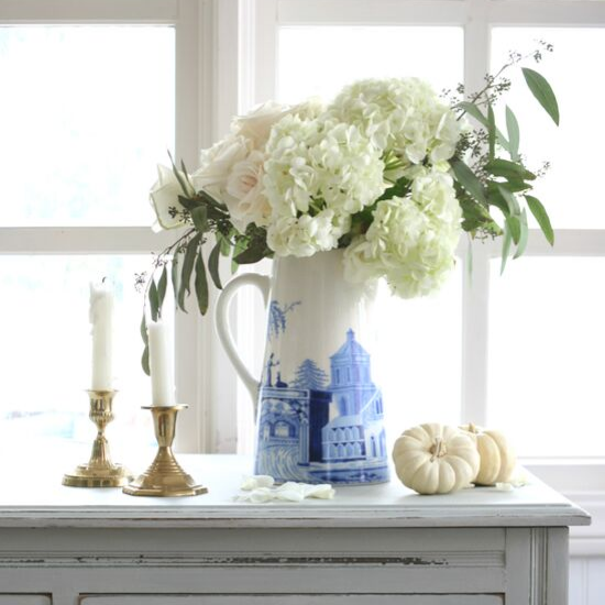 Light shades of hydrangeas, roses with eucalyptus accents in a white pitcher with cobalt blue accents posed next to brass candlesticks and small white pumpkins on a distressed sideboard in front of a window.