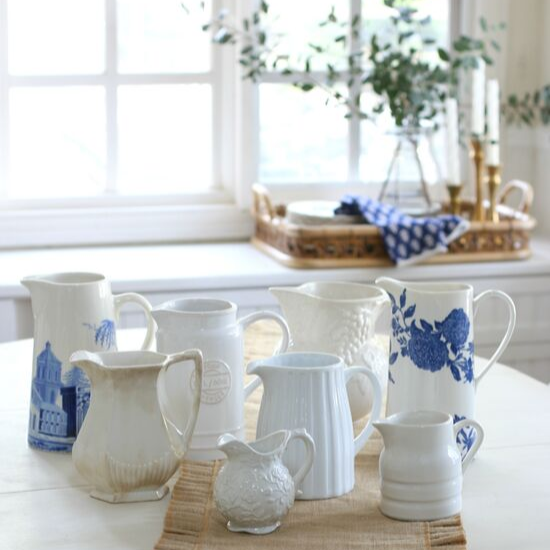 Collecting vintage pitchers in varying shades and shapes arranged on a dining table with a linen runner.