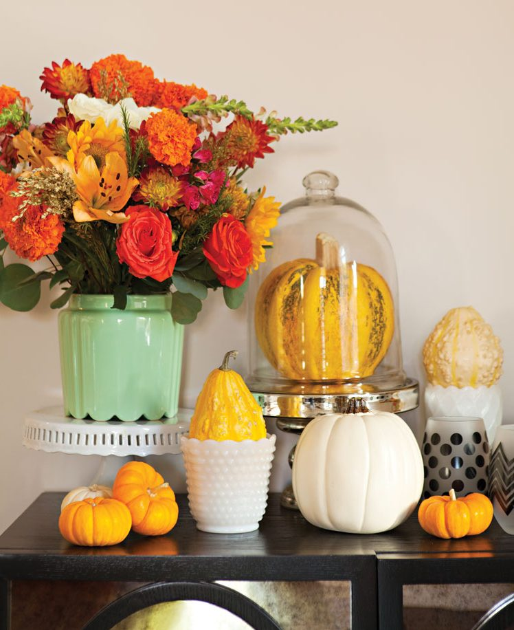 Black sideboard adorned with florals and various vases and gourds.