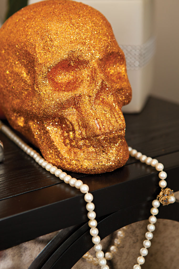 Bright orange skull covered in glitter and a strand of vintage pearls adorn a table as party decor.