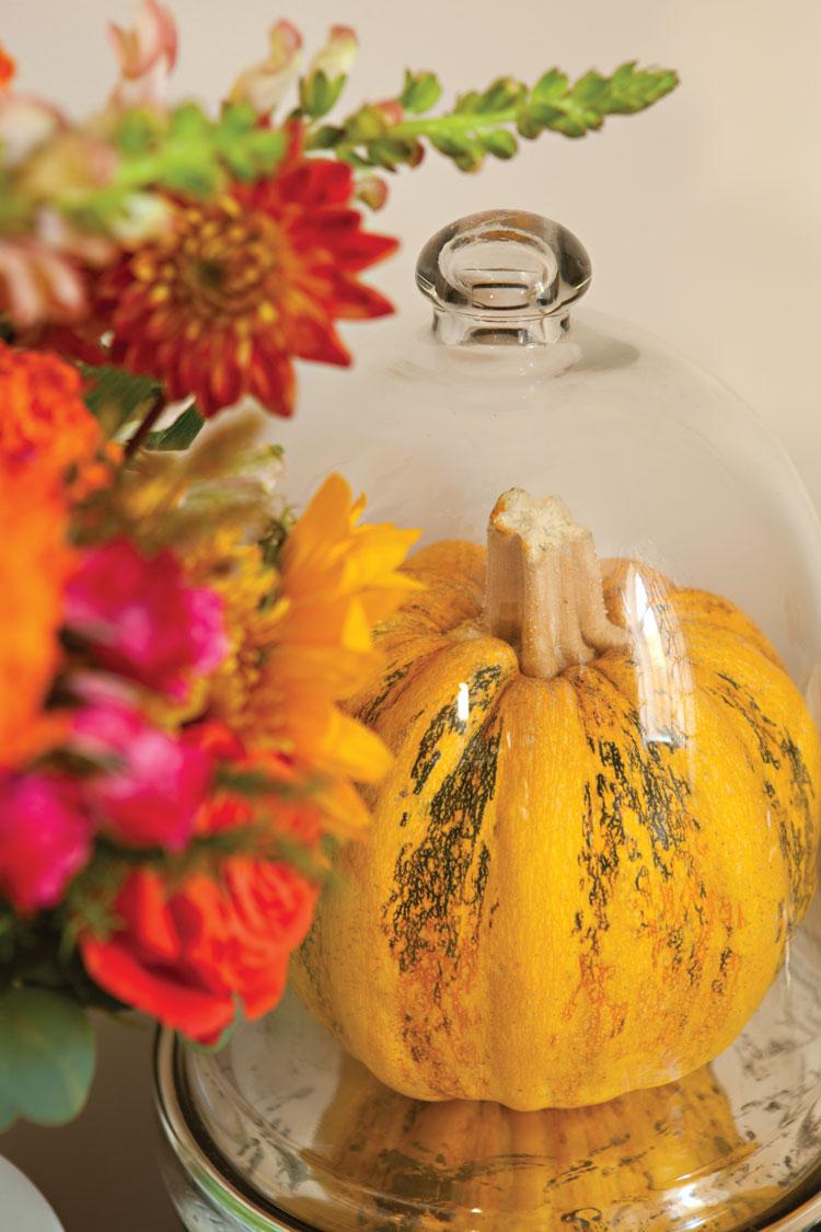 Bright floral centerpiece next to a pumpkin under a glass cloche.
