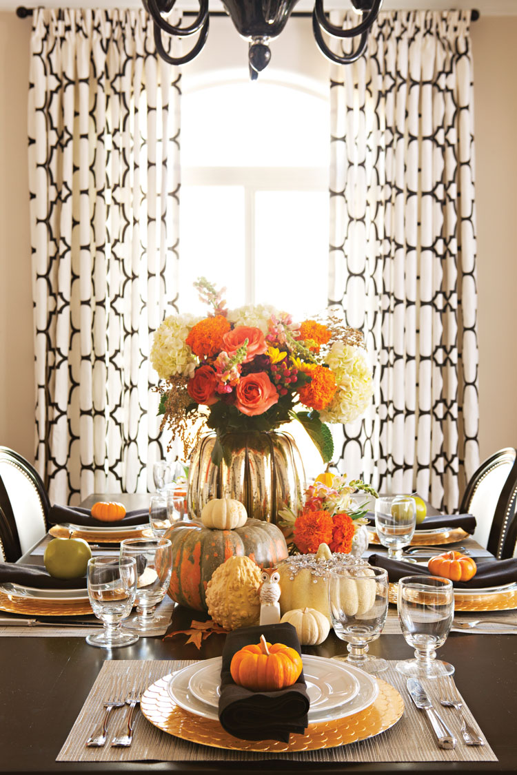 Halloween dinner party set for 5 guests with pumpkins, gourds and a large floral arrangement as the centerpiece of the tablescape.