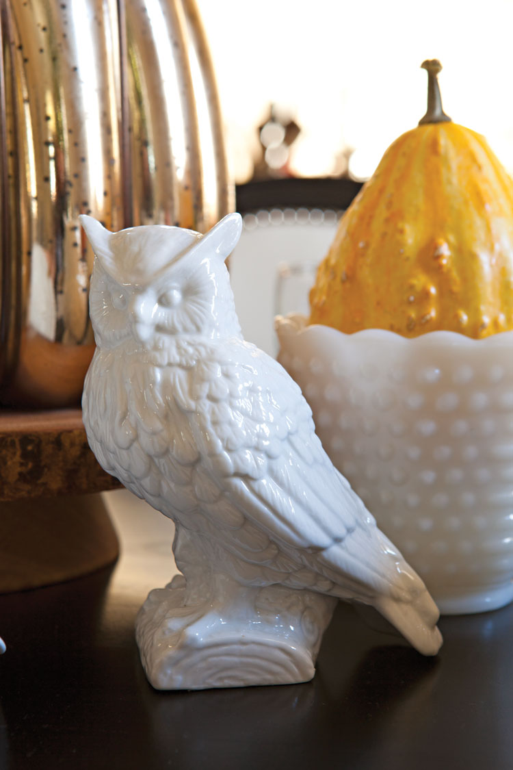 Centerpiece made up of a white porcelain owl figurine, a milk glass vase filled with a gourd and a gold metallic pumpkin.
