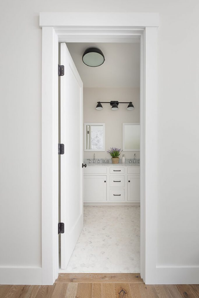 This bathroom shows how to match white paint with off-white paint. It has a white door and white cabinets with off-white flooring and walls.