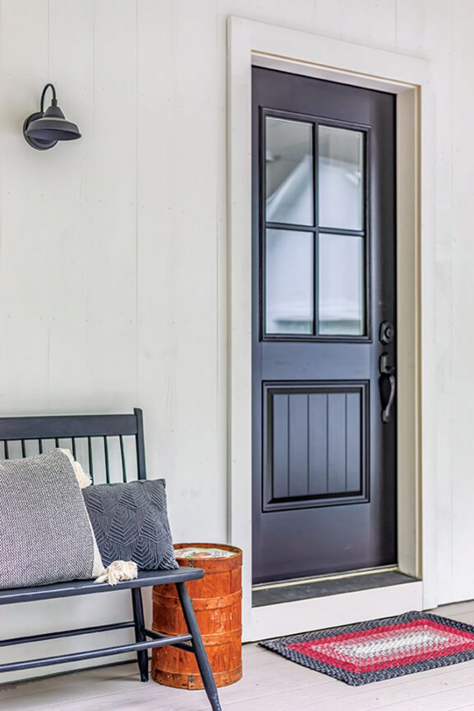 The exterior view of this house's front black door and bench shows how beautiful white painted siding looks with accent colors.