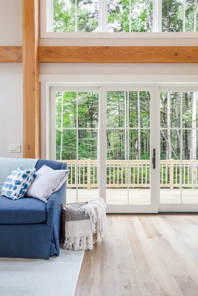 This living room has large windows and glass door that show how natural light makes white paint look lighter and brighter.