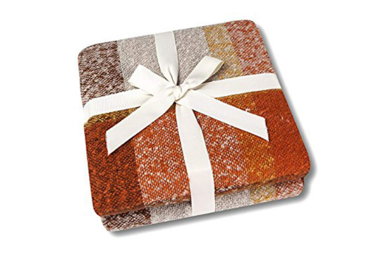 Orange and beige fluffy throw blanket, folded up and tied up with a white bow.