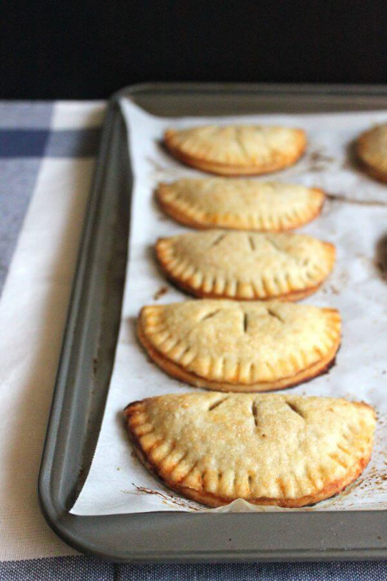 A baking tray lined with five small apple hand pies arranged on parchment paper.