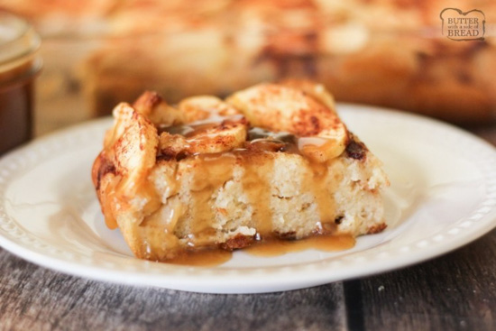 White glass plate with a generous serving of apple bread pudding with a caramel sauce topping.