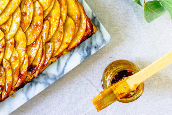 A marbled tray filled with fresh French Apple Tart pictured next to a jar topped with a gooey pastry brush.
