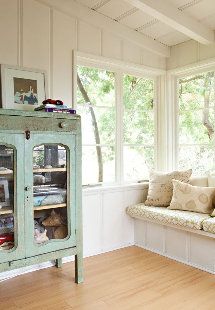 A vintage, soft green display cabinet in a loft with a light and bright window seat overlooking trees and nature outside.