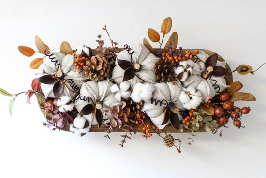 Dough bowl centerpiece on a white backdrop filled with natural autumnal decor.