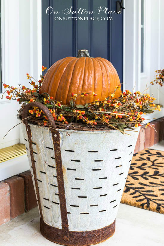 Rustic olive buckets filled with grapevines and a faux pumpkin, situated on a porch next to the front door.
