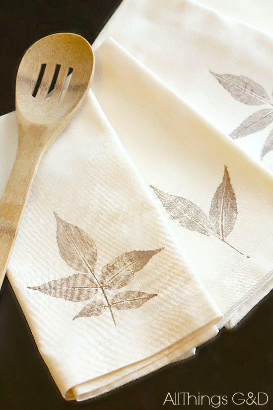 A set of four cream colored linen napkins each decorated with a hand stamped gold leaf and situated next to a slotted wooden spoon.
