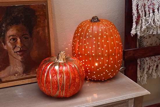 Two decorative pumpkins on a mantle next to a framed portrait.