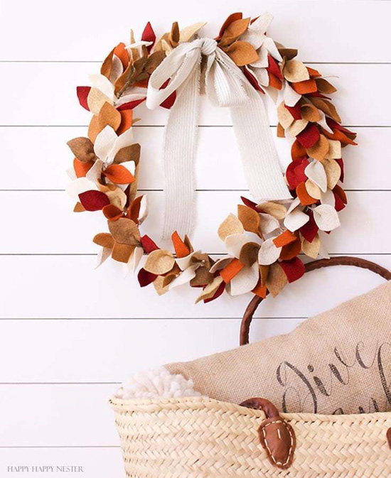 DIY fall craft, a hanging wreath covered in felt multicolored leaves in front of a white shiplap backdrop with a woven travel bag in the foreground.