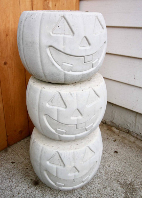 Set of 3 stacked identical cement pots in the shape of a halloween jack-o-lantern.