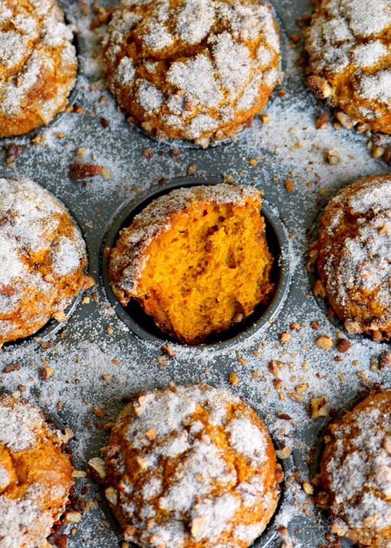 Metal muffin tin filled with pumpkin muffins and sprinkled with crunchy sugar, the middle muffin is pulled open so the center is viewable.
