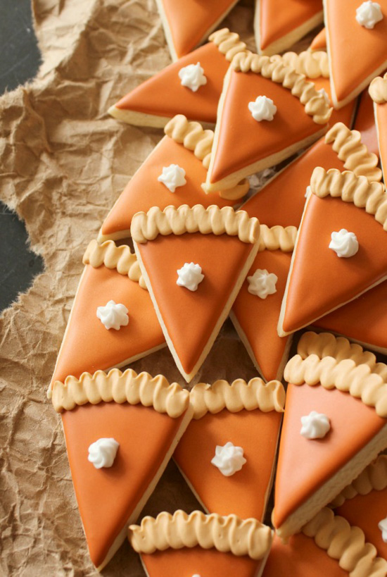 Beautifully designed sugar cookies in the shape of individual slices of pumpkin pie.