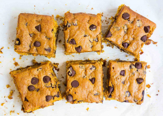 Six pumpkin, chocolate chip brownie squares viewed from above.