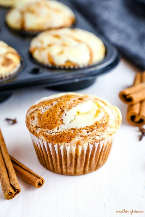 Pumpkin cream cheese muffins arranged in a muffin tin and cinnamon sticks as decoration.