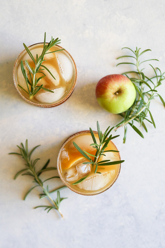 Aerial view of two cocktails in rocks glasses with rosemary sprigs placed around the glasses and an apple.